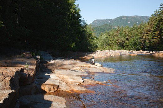 A hiker sitting on the side of the East Branch of the Pemigewasset River in the Pemigewasset Wilderness in Lincoln, New Hampshire USA : Stock Photo