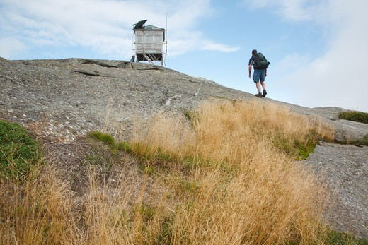Stock Photo: 1809-9524 Mount Cardigan State Park - A hiker near Cardigan Mountain Tower on Cardigan Mountain in Orange , New Hampshire USA. This fire tower was in operation from 1924-present