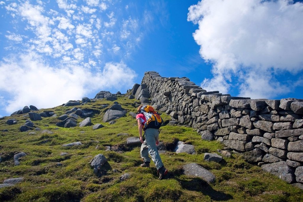 Mourne Mountains, Co Down, Ireland, Hiker beside the Mourne Wall on the slopes of Slieve Bearnagh : Stock Photo