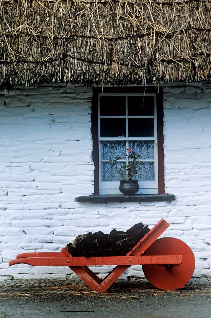 Wheelbarrow In Front Of A Window Of A Cottage, Bunratty Folk Park, Bunratty, County Clare, Republic Of Ireland : Stock Photo
