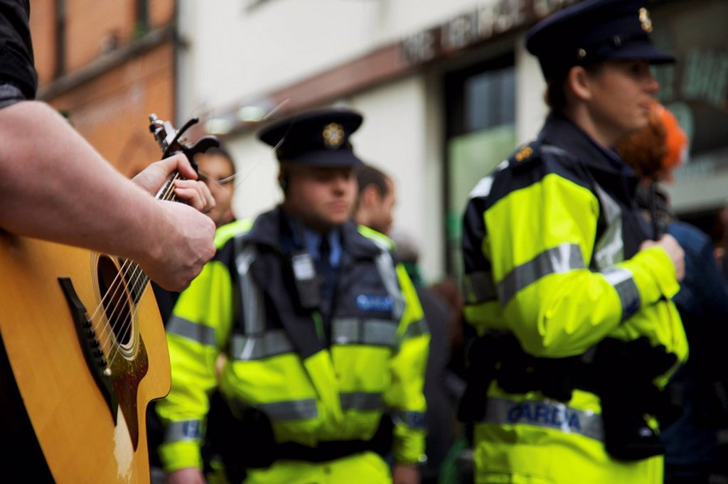 Stock Photo: 1812-11585 Dublin, Ireland, A Musician Plays His Guitar In The Street As The Police Pass By