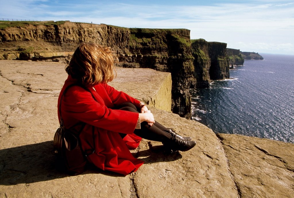Cliffs Of Moher, County Clare, Ireland; Woman Enjoying The View From A Cliff : Stock Photo