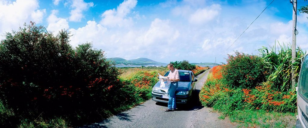 Cahirciveen, Co Kerry, Ireland, Man standing by his car on a country road : Stock Photo