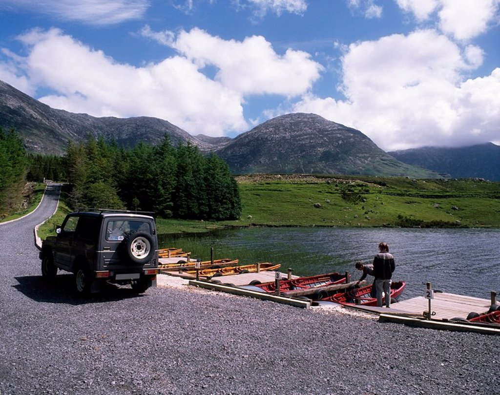Co Galway, Ireland, 4WD Jeep and people standing on a dock : Stock Photo