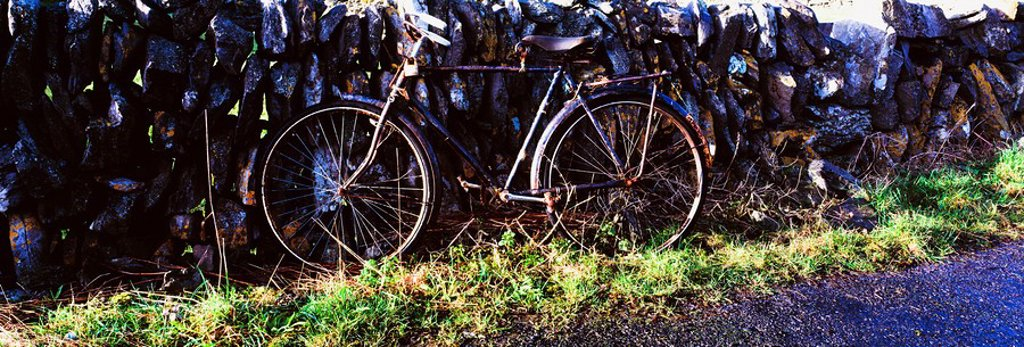 Stock Photo: 1812-9630 The Burren, County Clare, Ireland, Bicycle leaning against stone wall