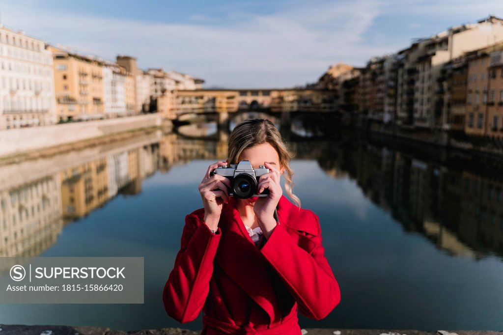 Stock Photo: 1815-15866420 Young woman taking a picture on a bridge above river Arno, Florence, Italy