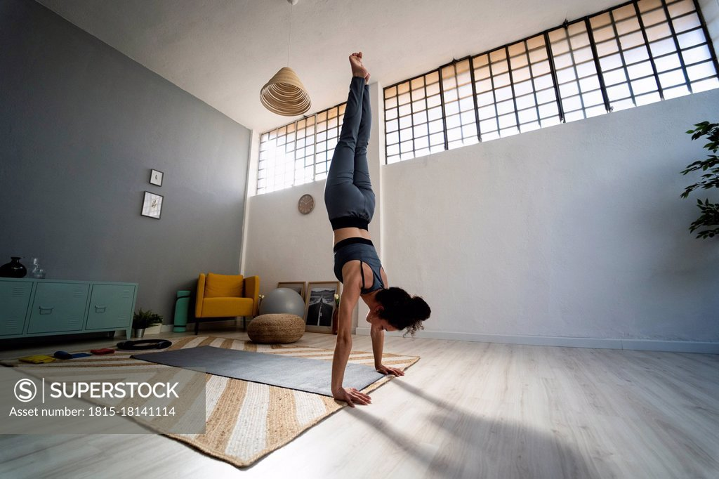 Stock Photo: 1815-18141114 Young woman balancing on hands in living room