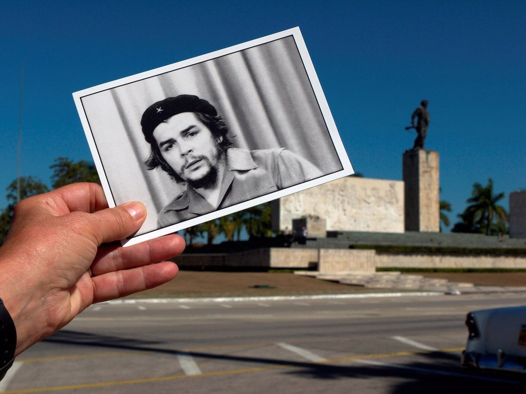 Cuba, Santa Clara, Close up of hand holding Che Guevara postcard with Memorial del Ernesto Che Guevara in background : Stock Photo