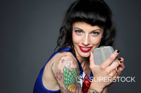 Stock Photo: 1815-107888 Close up of young woman with tattoo on her hand against grey background, singing, portrait
