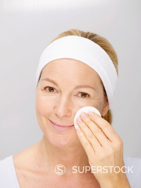 Mature woman cleaning face with cotton pad, close up : Stock Photo