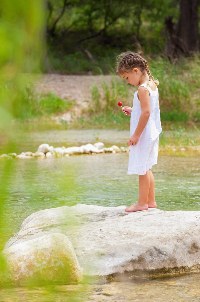 USA, Texas, Girl holding lollipop and standing on rock at Frio River : Stock Photo