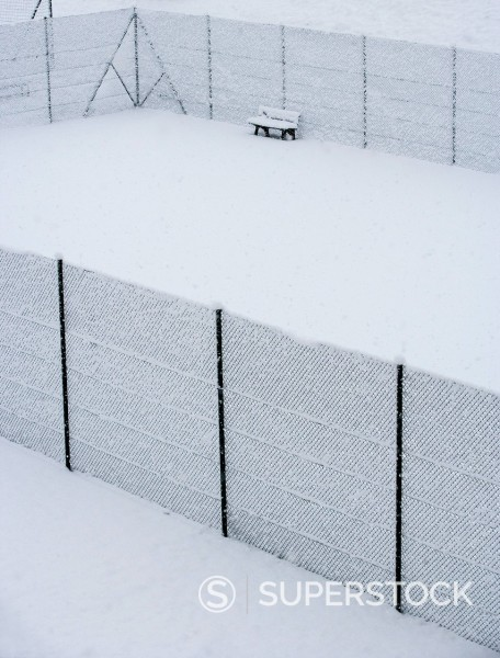Austria, Styria, Bench and fence covered with snow at tennis court : Stock Photo