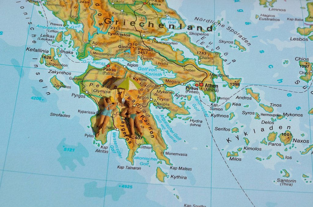 Stock Photo: 1815-128230 Greece, Couple of figurines laying on map