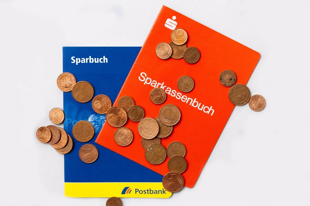 Stock Photo: 1815-128422 Savings bank book with euro coins on white background, close up