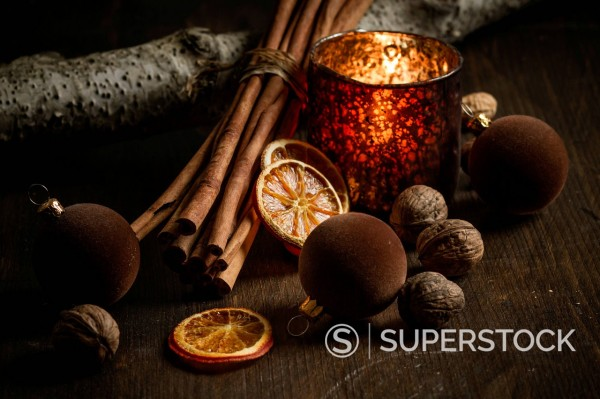 Christmas decoration with tea light candle, christmas tree balls, cinnamon sticks, slices of dried oranges and walnuts on wooden table, studio shot : Stock Photo
