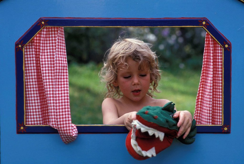Girl playing with crocodile hand puppet : Stock Photo