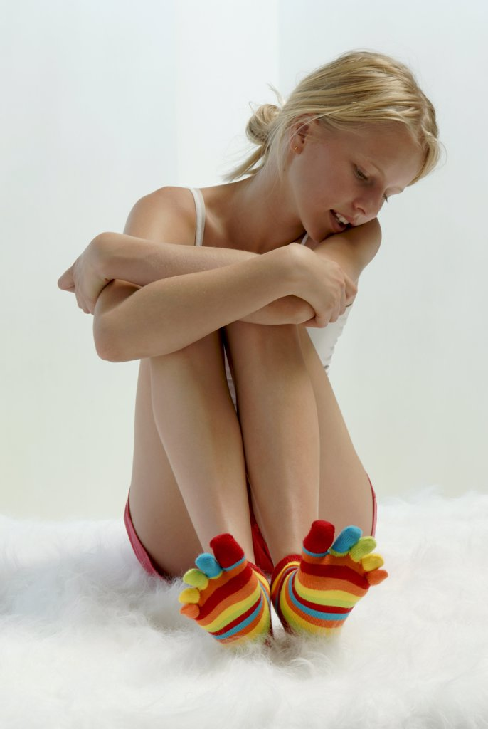 Girl with striped socks sitting on bed : Stock Photo