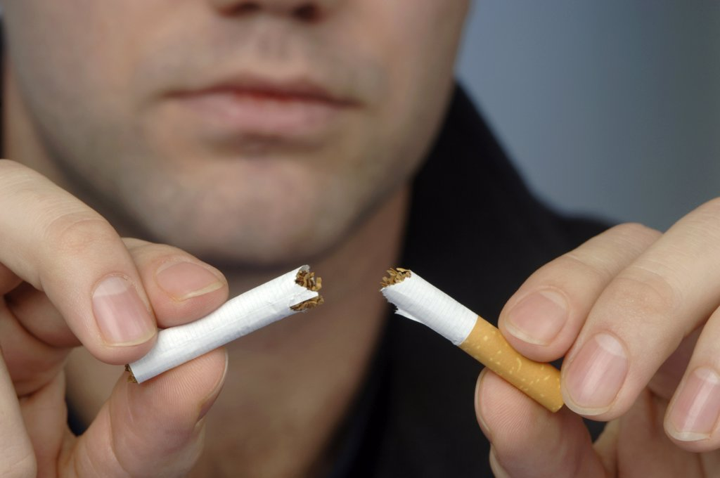 Stock Photo: 1815-40670 Man breaking up cigarette