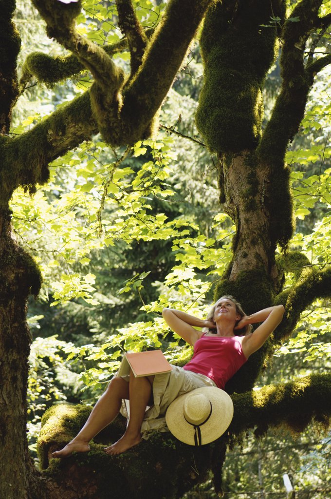 Stock Photo: 1815-41285 Young woman with book, relaxing in forest
