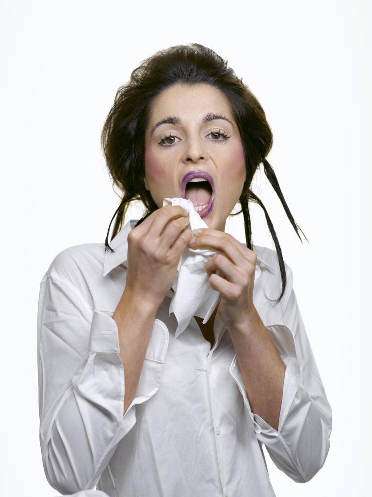 Young woman wearing white blouse, removing make-up : Stock Photo