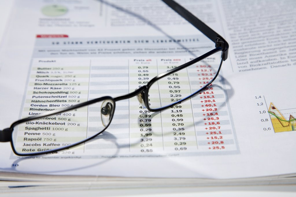 Glasses on business journal, close-up : Stock Photo