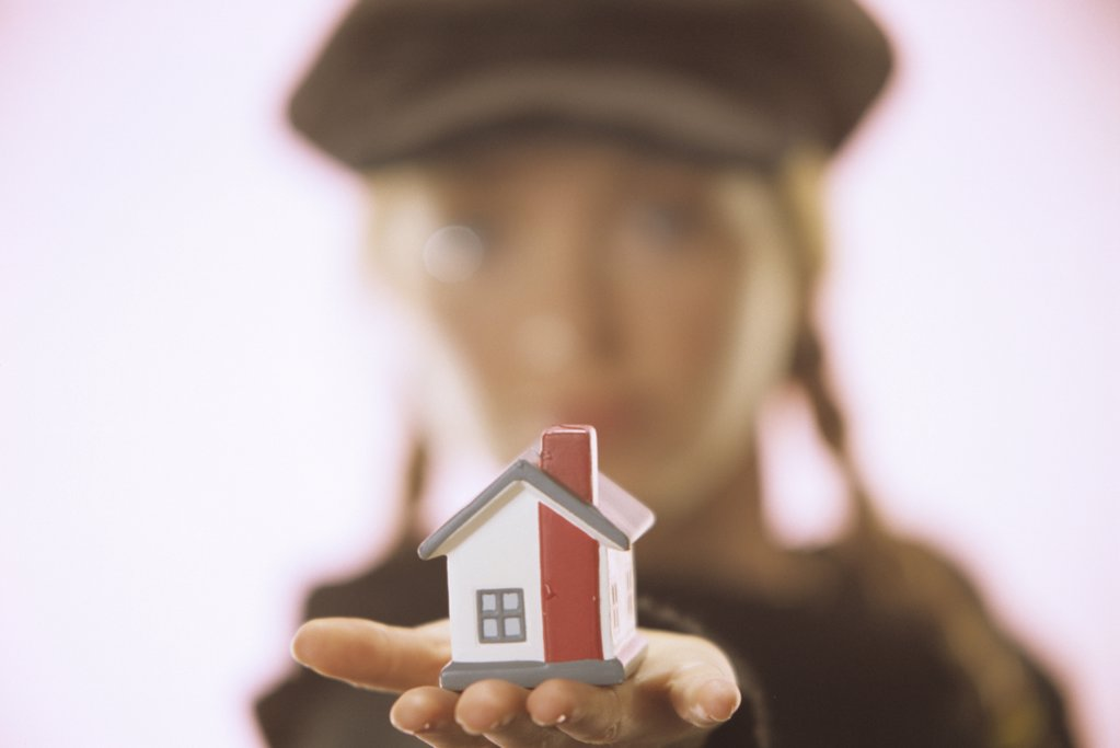 Young woman with toy house in her hand : Stock Photo