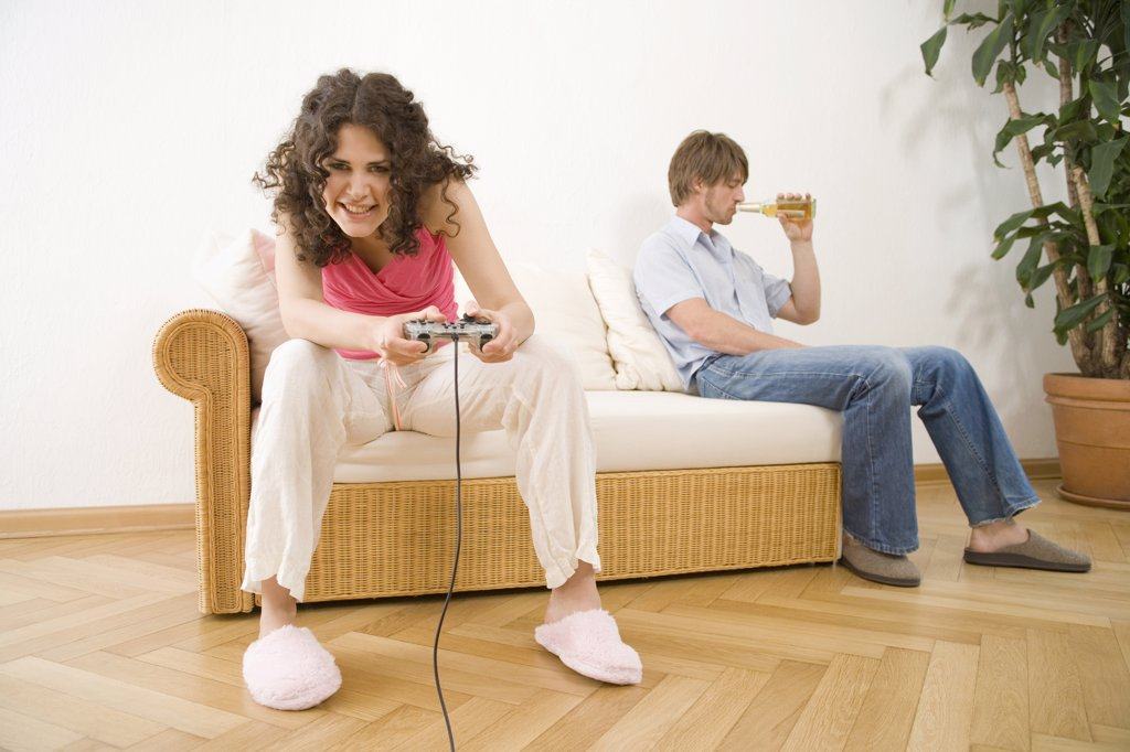 oung woman playing game with hand held controls, by man sitting on sofa : Stock Photo
