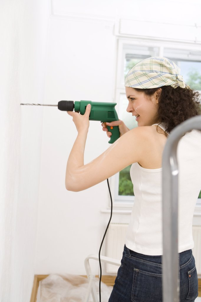 Stock Photo: 1815-43804 Young woman using drill