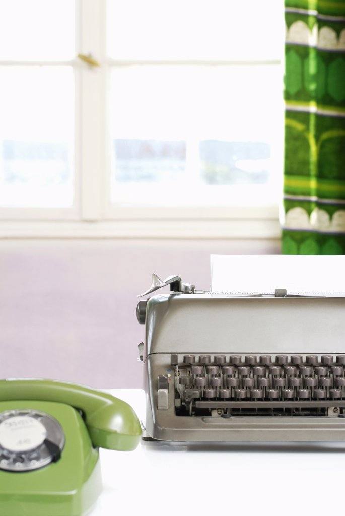 Office desk with phone and typewriter, close-up : Stock Photo