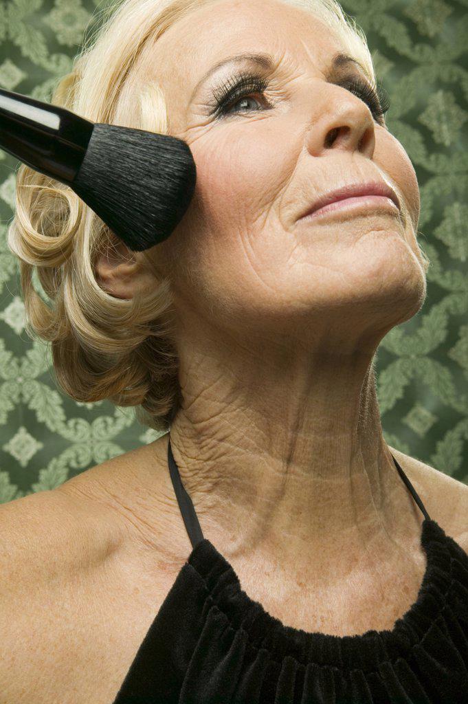 Elder lady with make up brush : Stock Photo