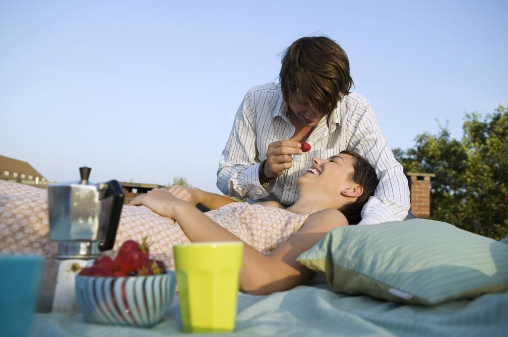 Stock Photo: 1815-44647 Young couple eating strawberries, outdoors