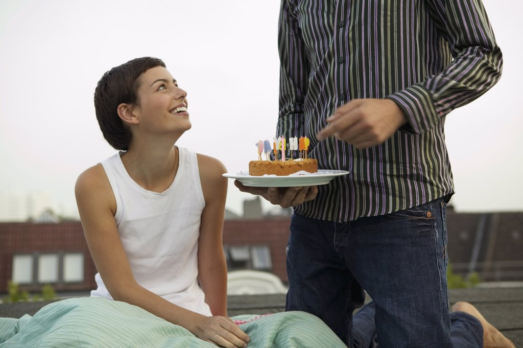 Stock Photo: 1815-44683 Young man giving birthday cake to woman