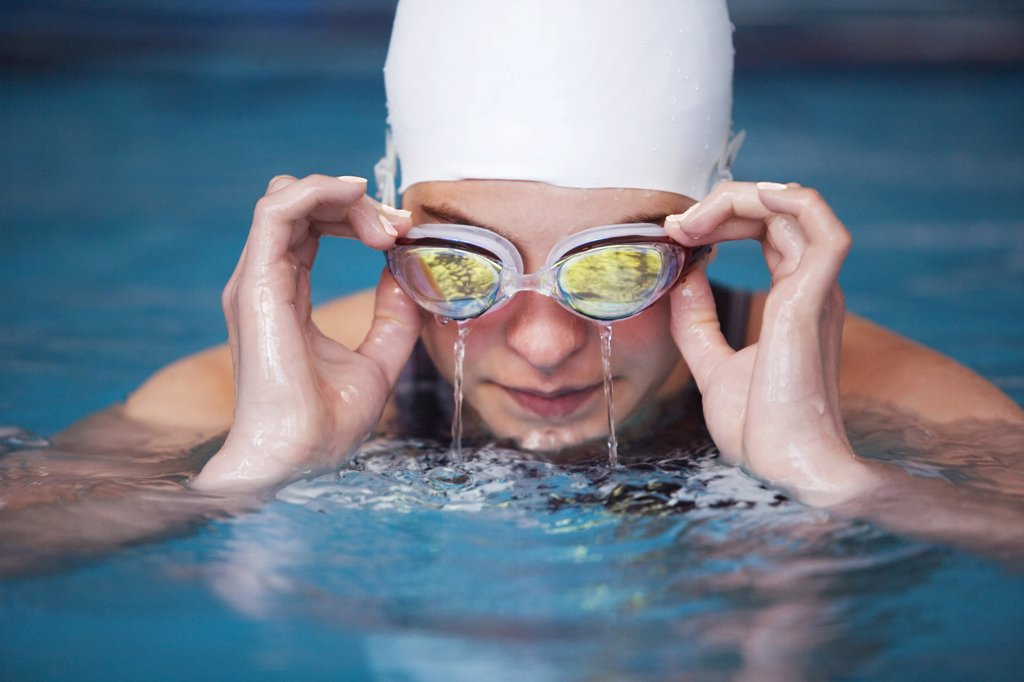Female swimmer emptying goggles : Stock Photo
