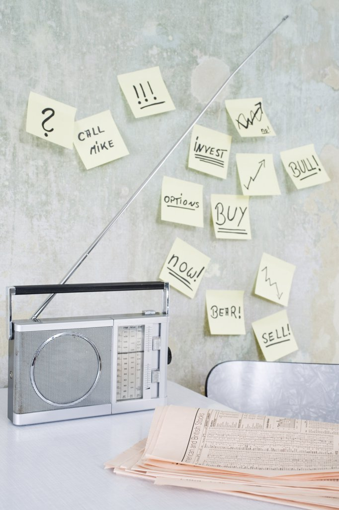 Radio and newspaper on table, adhesive notes on wall : Stock Photo