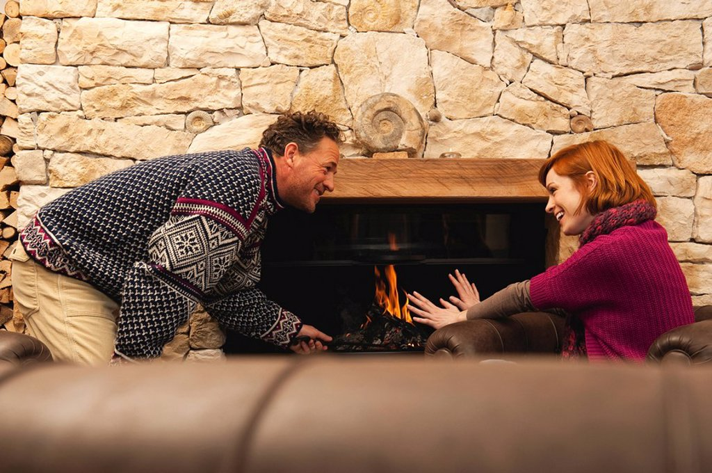 Couple in living room by fireside, having a good time : Stock Photo