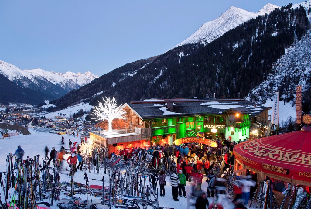 Stock Photo: 1815-89550 Austria, Tyrol, St. Anton am Arlberg, Mooserwirt, People skiing near ski hut in winter at dusk