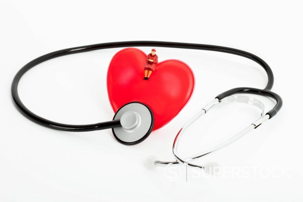 Figurine sitting on heart with stethoscope on white background : Stock Photo