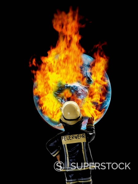 Fireman figurine in front of earth with burning fire, close up : Stock Photo