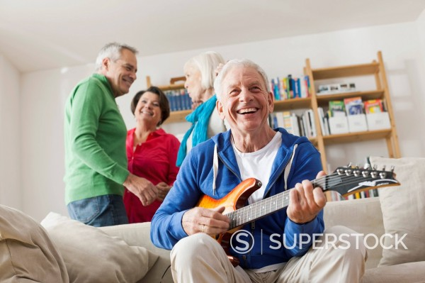 Germany, Leipzig, Senior man playing electric guitar, man and woman in background : Stock Photo