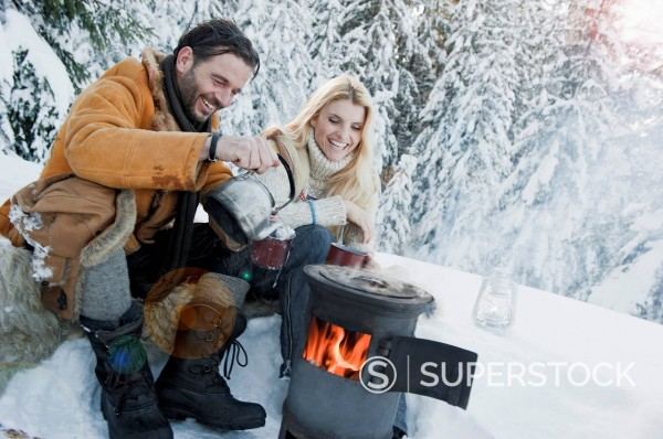 Stock Photo: 1815R-101494 Austria, Salzburg County, Couple sitting near camping stove and drinking tea