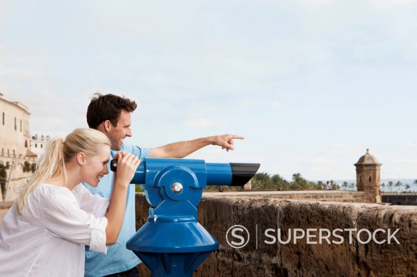 Spain, Mallorca, Palma, Couple looking through telescope : Stock Photo