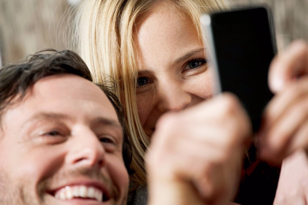 Couple watching cell phone, smiling, close up : Stock Photo