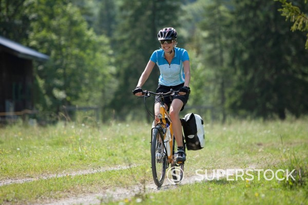 Austria, Tyrol, Young woman cycling through single track : Stock Photo