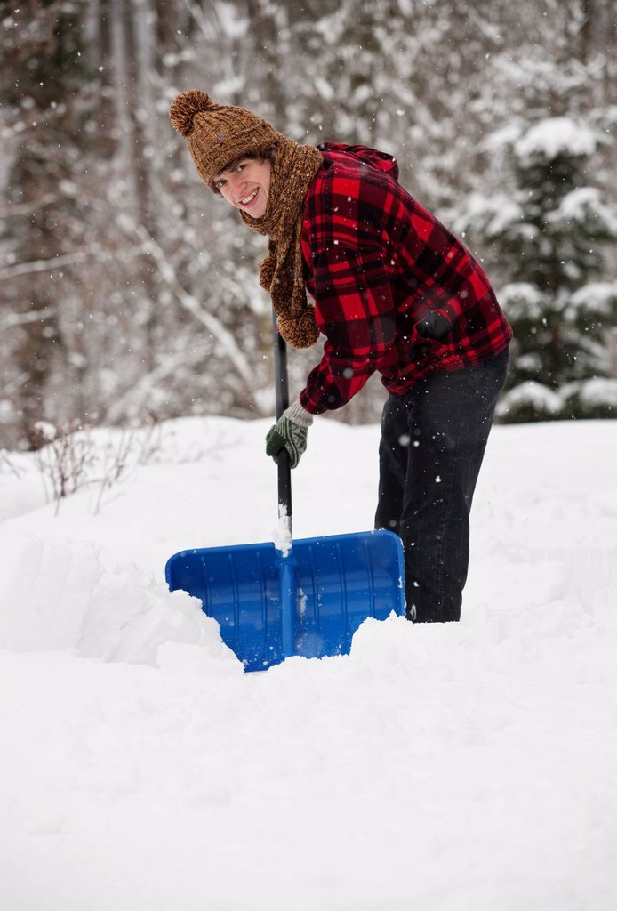Stock Photo: 1815R-102181 Austria, Young man shoveling snow, portrait