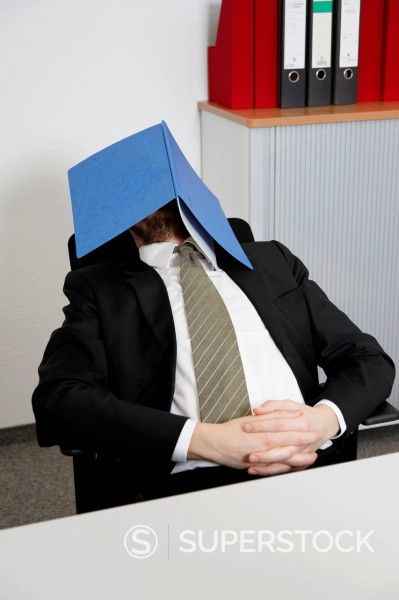 Germany, Businessman sleeping with file on face : Stock Photo