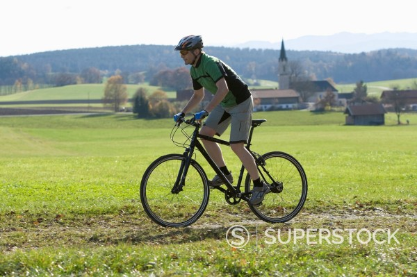 Germany, Bavaria, Mature man riding bicycle : Stock Photo