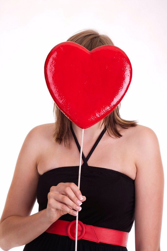 Stock Photo: 1815R-103467 Young woman holding heart in front of her head