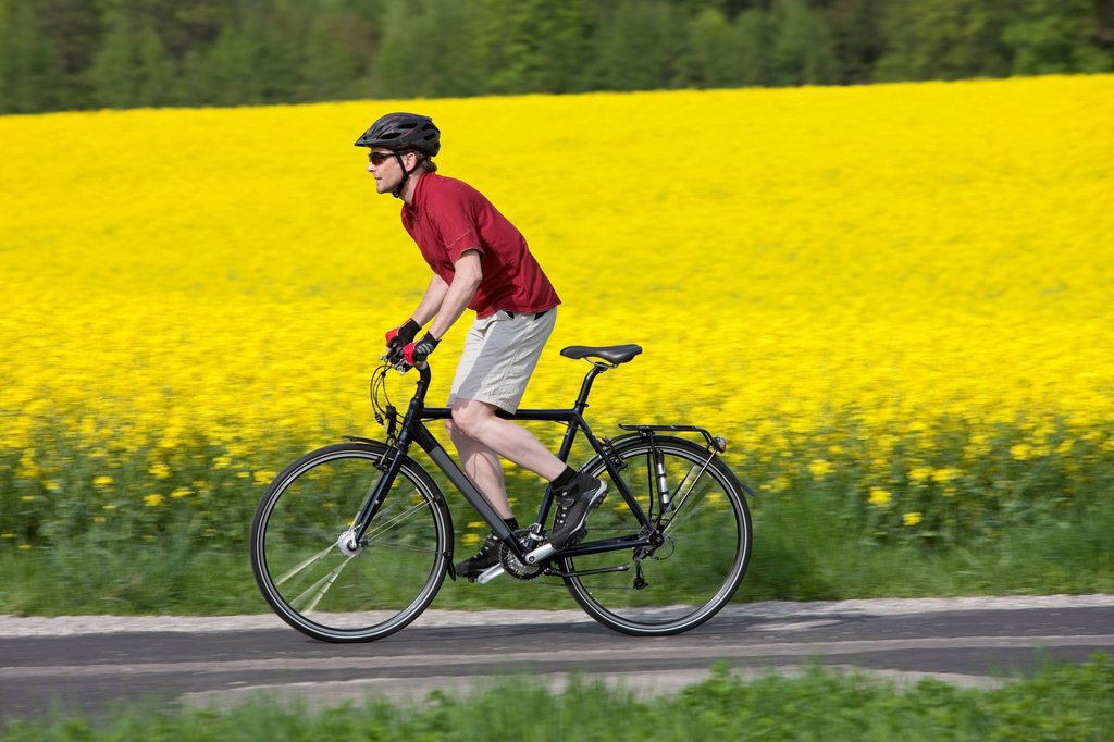 Germany, Bavaria, Starnberg, Mature man cycling through country road : Stock Photo