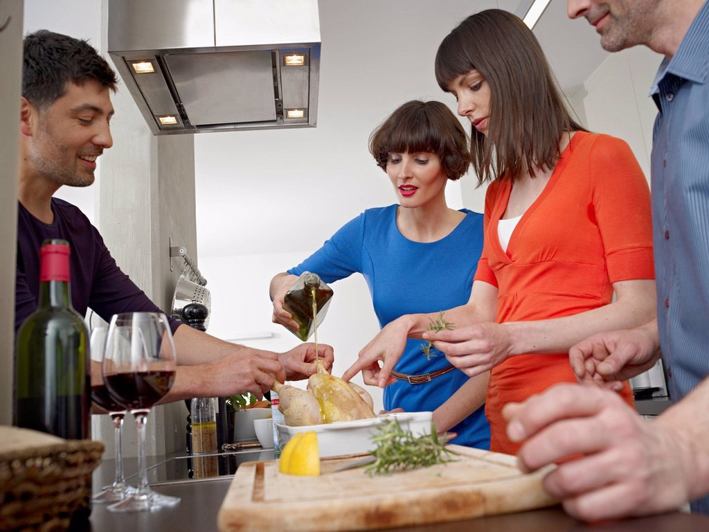 Stock Photo: 1815R-103499 Germany, Cologne, Men and women cooking together in kitchen