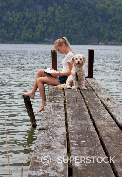Austria, Teenage girl reading book beside dog on jetty : Stock Photo